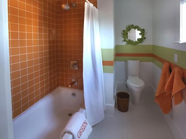 Baie cu peretele cu cada portocaliu si restul peretilor albi si brau verde cu oranj