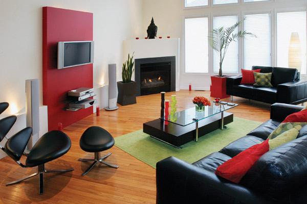 Living cu canapea neagra din piele covor verde si accesorii rosii