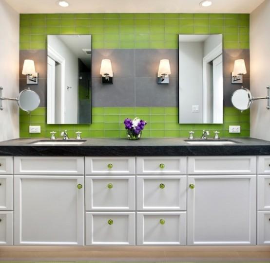 Perete placat cu faianta verde si gri si mobila de baie alba cu manere verzi